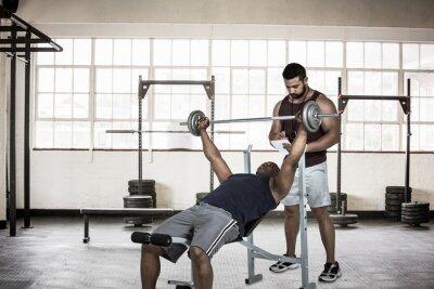 Trainer helfen muskulösen Mann, die Hantel zu heben