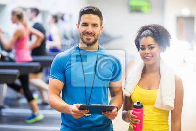 Trainer und Client lächelnd in die Kamera