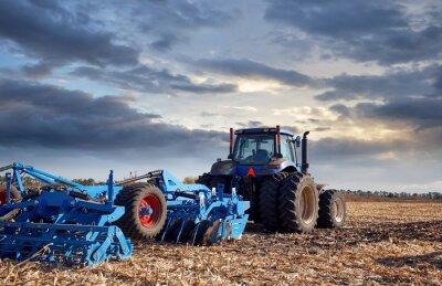 Bild Traktor, der auf dem Gebiet bei Sonnenuntergang arbeitet