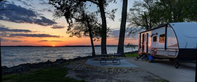 Bild Travel trailer camping at sunset by the Mississippi river in Illinois at sunset panorama
