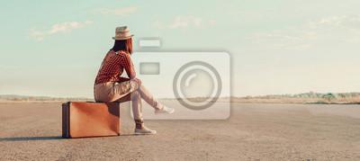Bild Traveler girl sitting on a suitcase on road