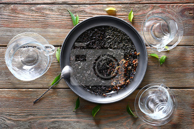 Bild Tray with dry tea leaves on wooden table