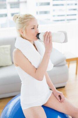 Trinkwasser der geeigneten Frau beim Sitzen auf Übungsball