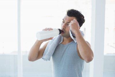 Trinkwasser des Mannes beim Abwischen schwitzt mit Tuch im Eignungsstudio