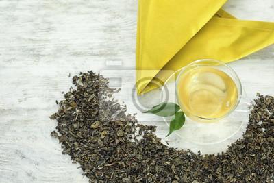 Bild Trockene grüne Teeblätter und Schale aromatisches Getränk auf hölzernem Hintergrund