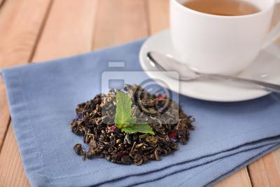 Bild Trockene grüne Teeblätter und Schale aromatisches Getränk auf Tabelle