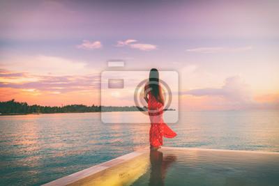 Bild Tropical beach paradise travel vacation woman woman at dusk relaxing on luxury infinity pool resort hotel holiday. Summer getaway honeymoon destination.
