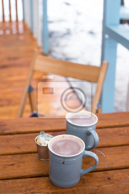 Bild Two cups of cocoa and sugar bucket on a wooden table on the outdoor winter terrace. Hot sweet drink .to warm up on a snowy day