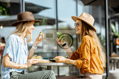 Bild Two female best friends eating healthy food while sitting together on a restaurant terrace on a summer day