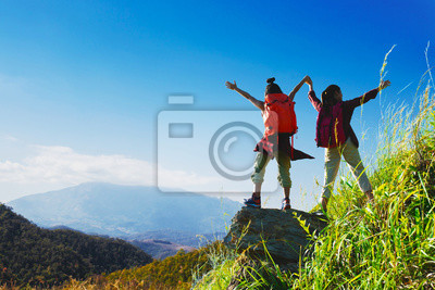 Bild Two female hikers enjoying on the top of cliff mountian.