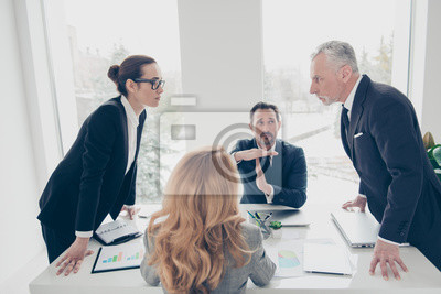 Bild Two stylish business persons in suits having disagreement, war, conflict, standing near desktop in front of each other, face to face with disrespect expression, partner showing stop sign with hands