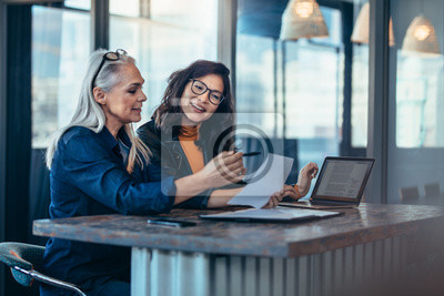 Bild Two women analyzing documents at office