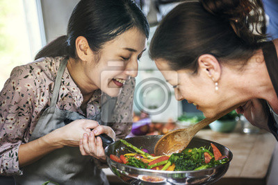 Bild Two women cooking healthy vegetables in a pan