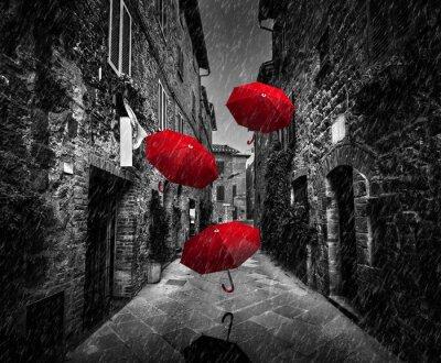 Bild Umrbellas fliegen mit Wind und regen auf dunkle Straße in einer alten italienischen Stadt in der Toskana, Italien