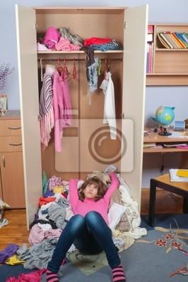 Untidy Teenager-Mädchen auf Stapel der faltige Kleidung liegen