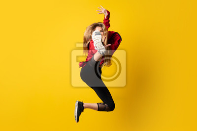 Bild Urban Ballerina dancing over isolated yellow background and jumping