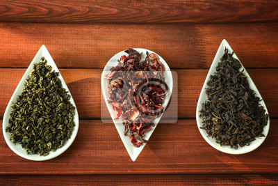 Bild Variety of dry tea in plates on wooden background