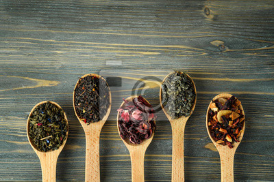 Bild Variety of dry tea in spoons on wooden background