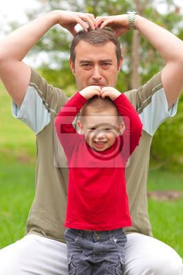 Vater imitiert seinen Sohn, während die Zeit in den Park