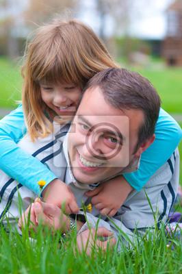 Vater und Tochter, die Spaß im Gras