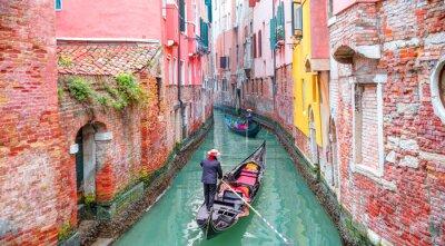 Bild Venetian gondolier punting gondola through green canal waters of Venice Italy