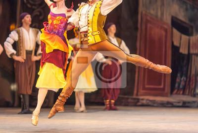 Vergnügen, Gnade, Tanzkonzept. Ballett-Duett von männlichen und weiblichen Tänzern, gekleidet in hellen, mehrfarbigen Kostümen in gelben Tönen, die über der Bühne schwimmen, die sich gegenseitig halte
