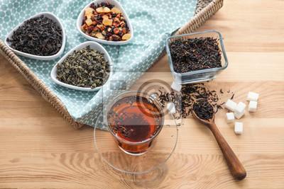 Bild Verschiedene Arten von trockenen Teeblättern und von Schale aromatischem Getränk auf Holztisch