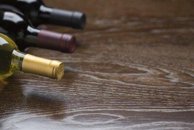 Bild Verschiedene Weinflaschen auf reflektierende Holzoberfläche Abstract