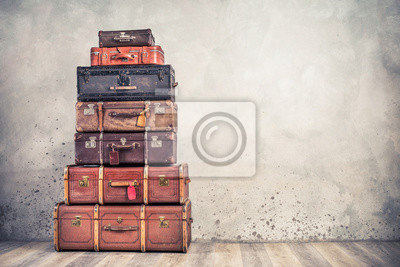 Bild Vintage classic outdated trunks luggage with tags, old antique leather suitcases tower front concrete wall background. Travel baggage concept. Retro style filtered photo