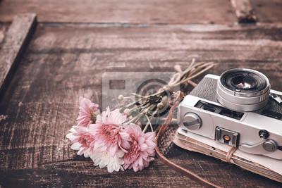 Bild Vintage-Kamera mit Blumenstrauß auf alten Holz Hintergrund - Konzept der Nostalgie und Erinnerung im Frühjahr Jahrgang Hintergrund