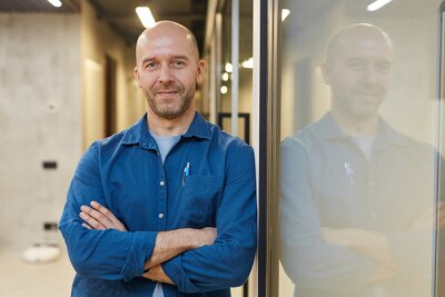 Bild Waist up portrait of mature bald man smiling at camera while standing with arms crossed and posing confidently leaning against wall, copy space