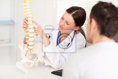 Weibliche Arzt zeigt auf Knochen in der Wirbelsäule