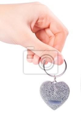 Weibliche Hand, die Metallanhänger in der Form des Herzens