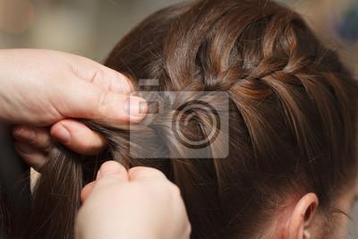 Bild Weibliche Hände flechten dunkles Haar, Nahaufnahme.