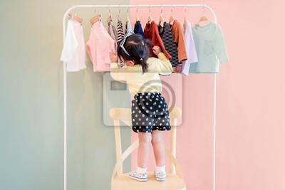 Bild Weichzeichnung eines zwei Jahre alten Kindes, das ihre eigenen Kleider vom Kinderstoff-Zahnstange wählt