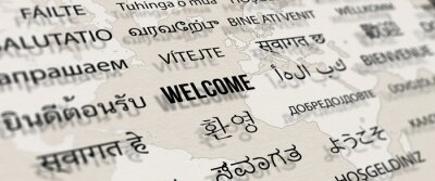 Bild Welcome in different language on paper with world map background. Depth of field image. Words cloud concept.