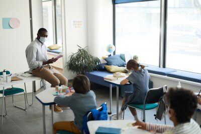 Bild Wide angle portrait of African-American male teacher wearing mask in school classroom, covid safety measures, copy space