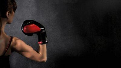 Bild Woman Boxer Bizeps mit Red Boxhandschuh auf schwarzem Hintergrund, hoher Kontrast mit gesättigter Grunge-Filter