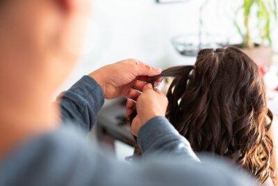 Bild Woman braiding girls hair.