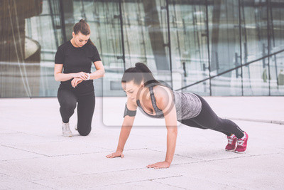 Bild Woman doing push-ups exercises with her personal trainer