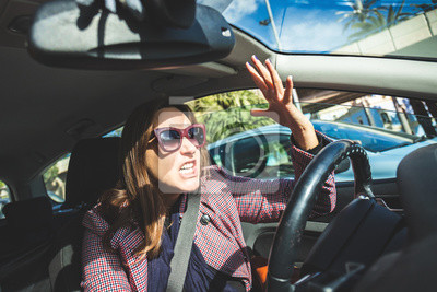 Bild Woman driving screaming stressed in traffic. Girl cursing and screaming at the transit drivers from inside the car passing through stress and hatred