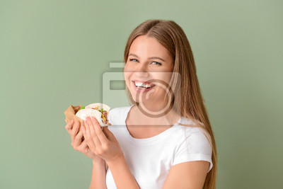 Bild Woman eating tasty taco on color background