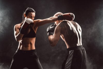 Bild Woman exercising with trainer at boxing and self defense lesson, studio, smoke on background. Female and male fight