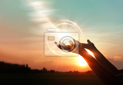 Bild .Woman hands praying for blessing from god on sunset background