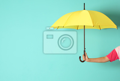 Bild Woman holding beautiful umbrella on color background with space for design