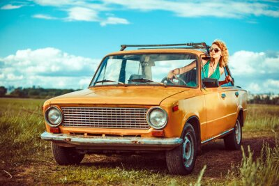 Bild Woman is driving an old yellow car. Rural background.