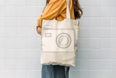 Bild Woman is holding bag canvas fabric for mockup blank template.