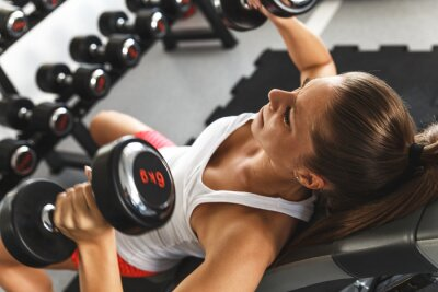 Bild Woman lifting  weights and working on her chest at the  gym