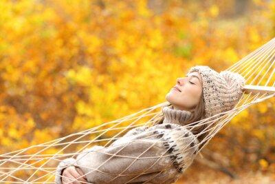 Bild Woman sleeping on hammock in a forest in autumn