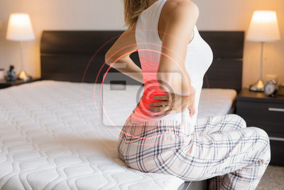 Bild Woman suffering from back pain because of uncomfortable mattress